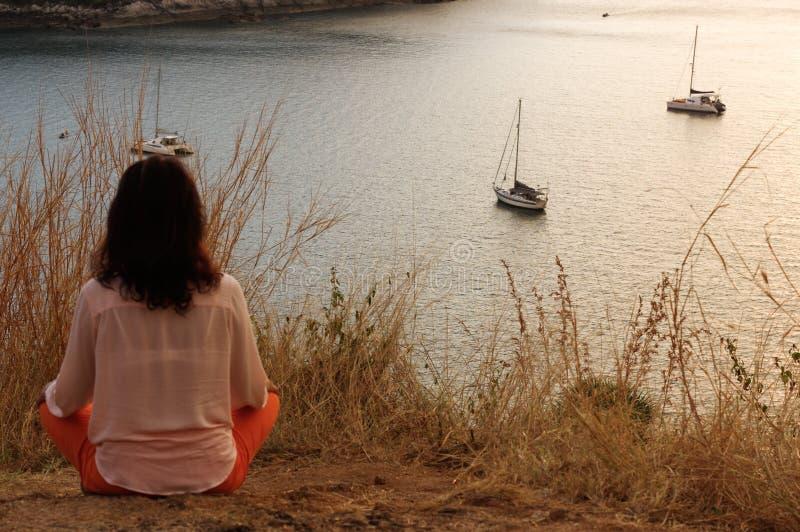 坐在瑜伽莲花在前面的凝思位置的女孩对海边在岩石观看太阳在金黄进来下来ho 免版税库存照片
