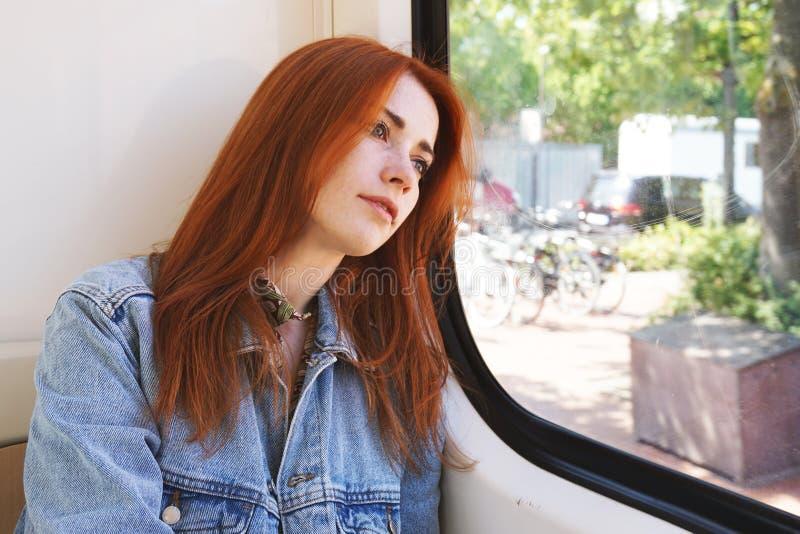 坐在电车或路面电车的年轻女人看在窗口外面 免版税图库摄影