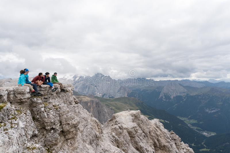 坐在白云岩的一个山峰壁架和看惊人的看法的五个年轻男性和女性远足者 免版税库存照片