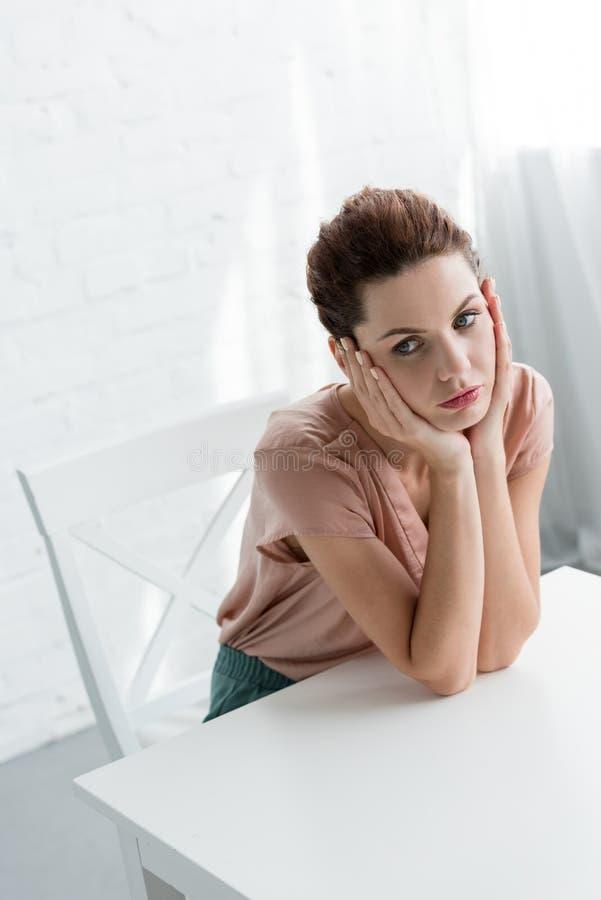 坐在白色前面的桌上的沮丧的年轻女人 免版税图库摄影