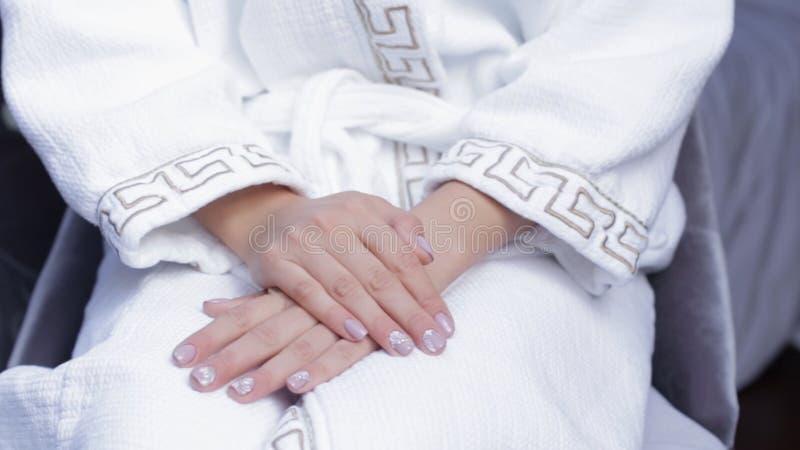 坐在白色外套的一把椅子的新娘 坐在有花的羊毛浴巾的妇女 新娘为婚礼之日做准备 库存图片