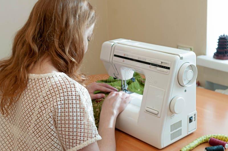 坐在白色缝纫机和运作在窗口附近的Eamstress 免版税库存图片