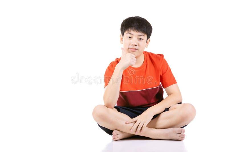 坐在白色背景的画象年轻亚裔男孩 免版税库存照片