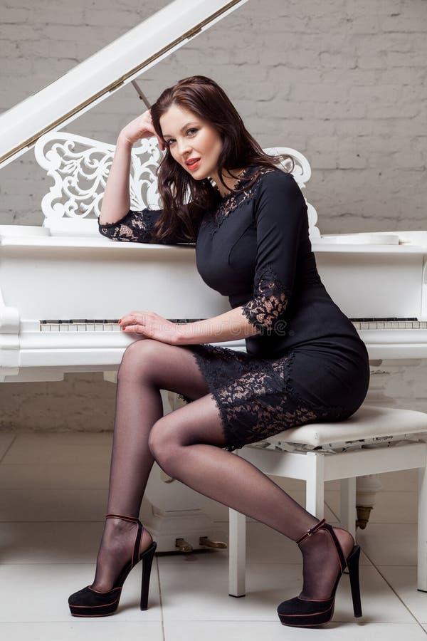 坐在白色钢琴附近,摆在和看照相机和微笑的鞋带黑经典礼服的肉欲的深色的妇女 库存照片