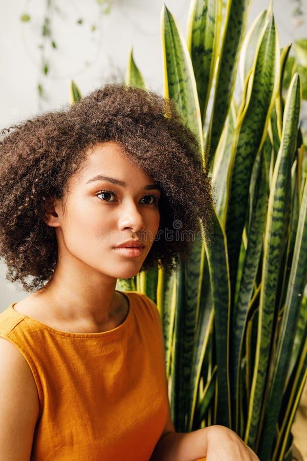 坐在百合科植物附近的美丽的年轻女人画象 图库摄影