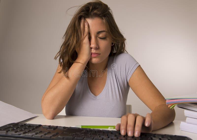 坐在看起来疲乏用尽和不耐烦的重音的计算机书桌的年轻可爱的学生女孩或职业妇女 库存照片