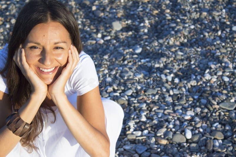 坐在石头上的女人,双手紧绷的脸 免版税库存图片