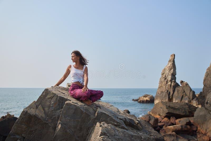 坐在石海滩的莲花坐的轻的夏天衣裳的一年轻女人 免版税库存图片