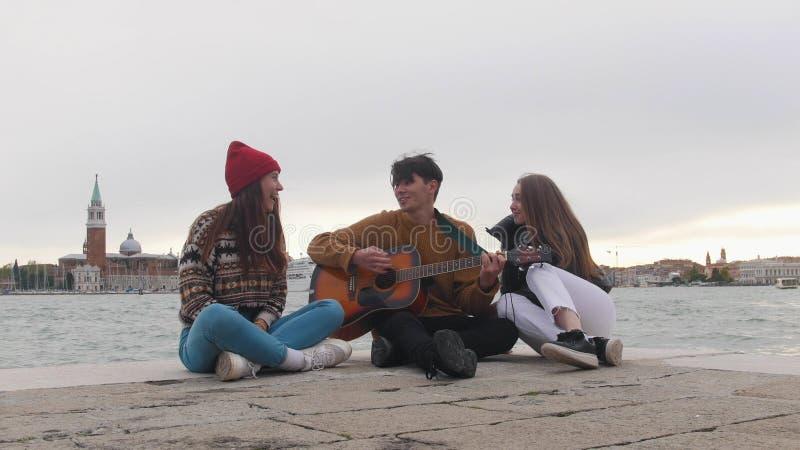 坐在码头和唱歌歌曲边缘的一个小组年轻朋友由吉他-威尼斯,意大利 免版税库存照片