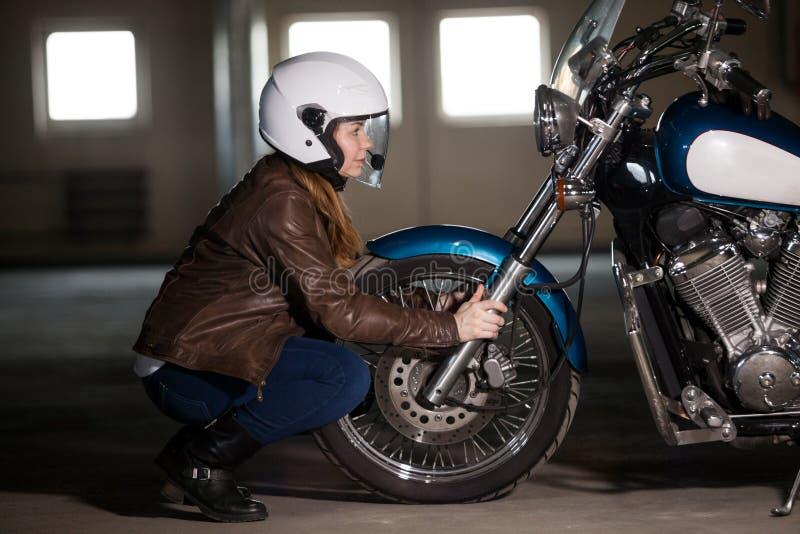 坐在砍刀自行车对面轮子,拿着轮子叉子和看在车灯灯的女性摩托车骑士 库存照片