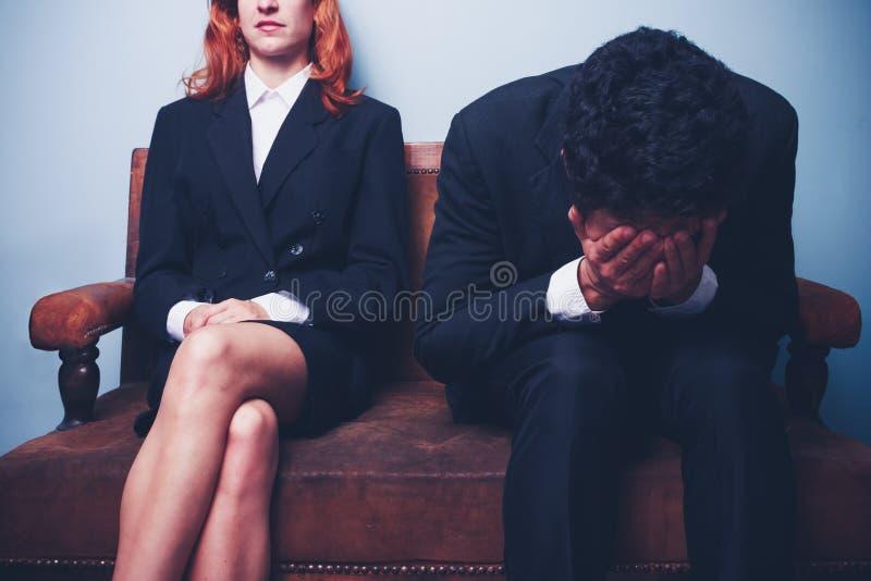 坐在确信的女实业家旁边的紧张的商人 免版税库存图片