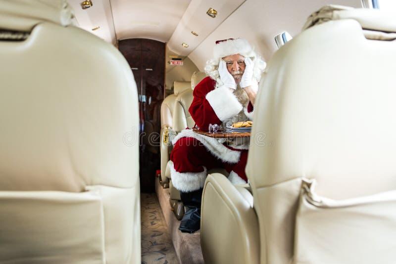 坐在私人喷气式飞机的圣诞老人 免版税图库摄影