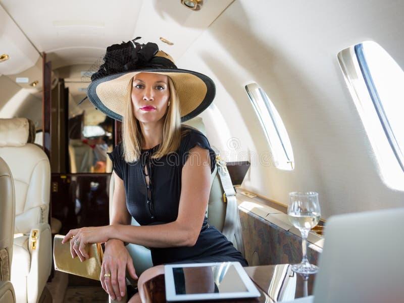 坐在私人喷气式飞机的富有的妇女 免版税库存照片
