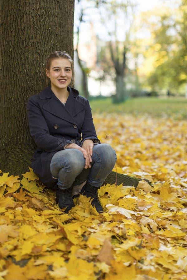 坐在秋天公园的女孩 走 免版税图库摄影