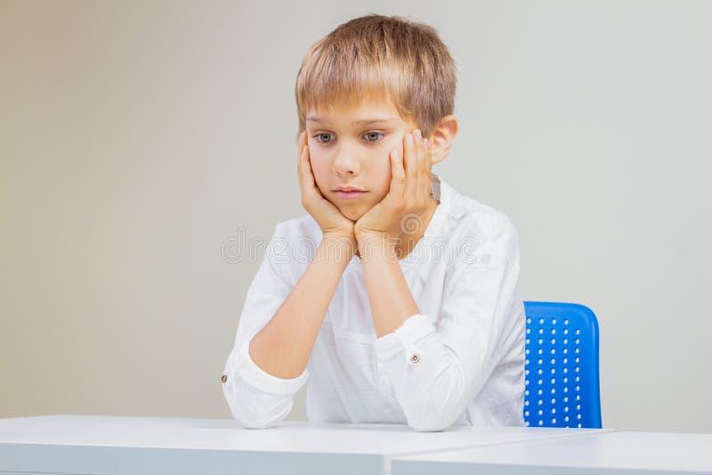 坐在空的白色书桌的想法的学童 免版税库存图片
