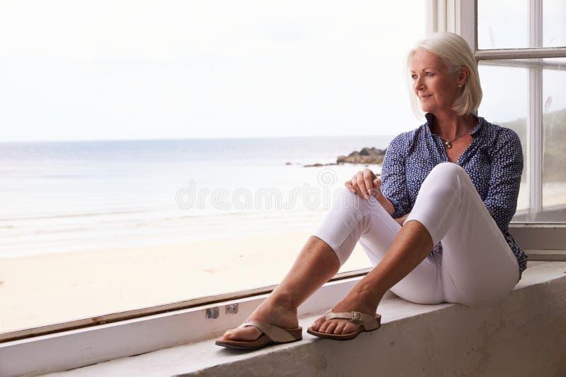 坐在窗口和看美好的海滩视图的妇女 免版税库存照片