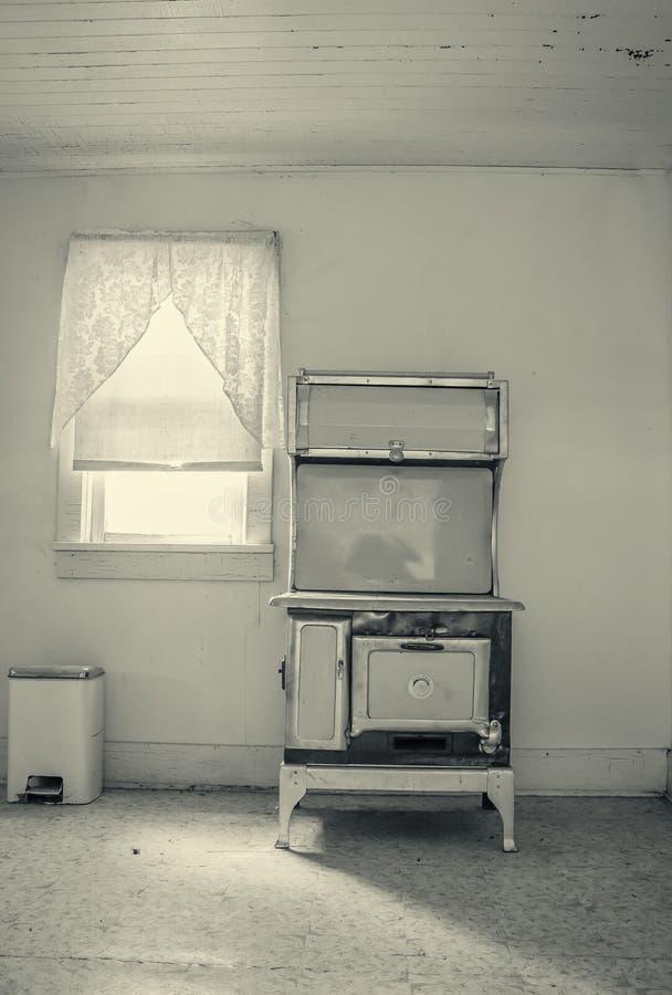 坐在窗口旁边的老古色古香的木燃烧厨师火炉 免版税图库摄影