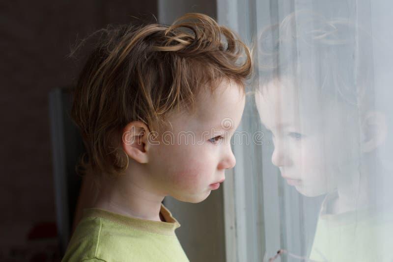 坐在窗口附近和考虑某事的小男孩 他有美丽的伟大的头发 逗人喜爱的婴孩 库存照片