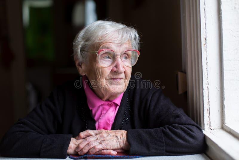 坐在窗口附近的一名年长妇女 画象 库存图片