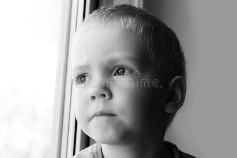 坐在窗口附近的可爱的矮小的白肤金发的孩子男孩 免版税库存照片