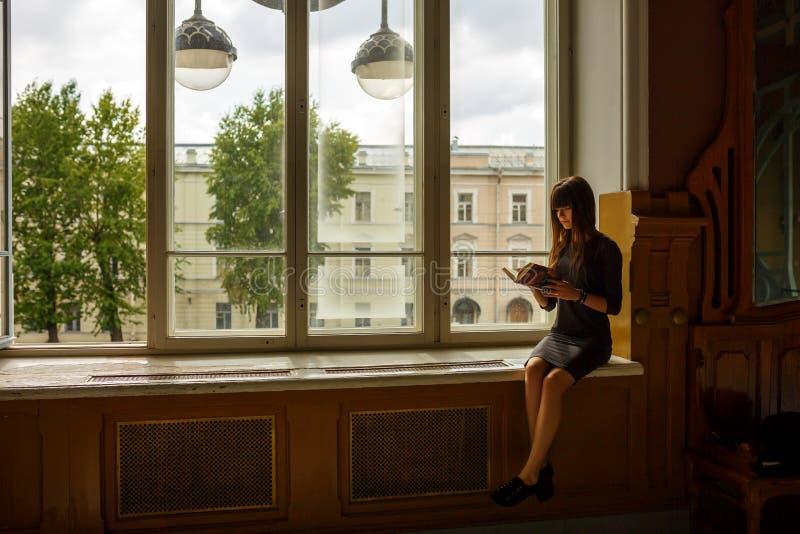 坐在窗口附近的女孩读书 免版税库存照片