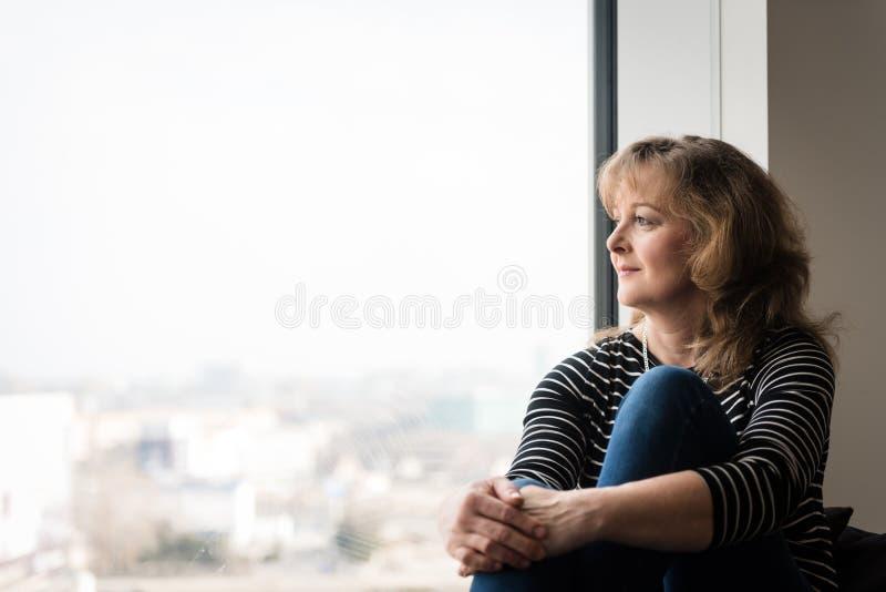 坐在窗口附近的成熟妇女,看外面 免版税库存照片