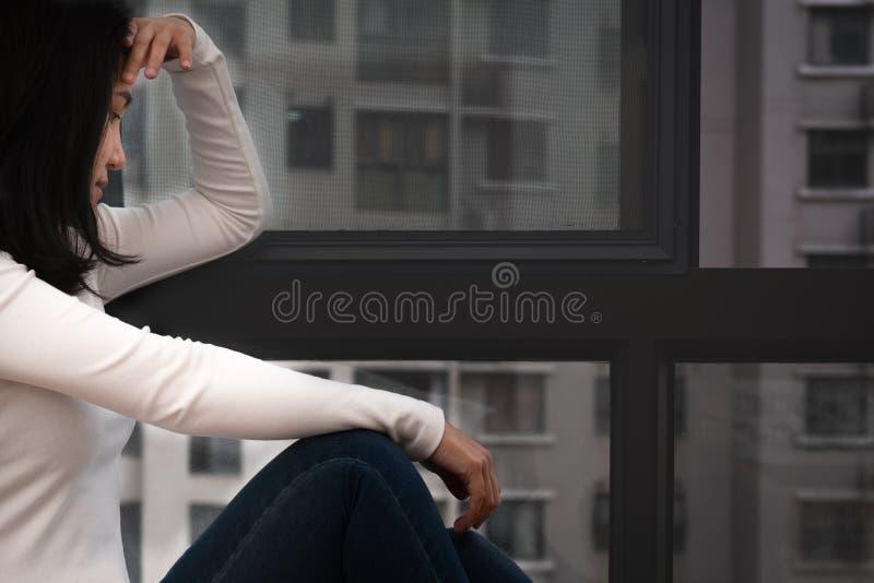 坐在窗口附近的沮丧的妇女,单独,悲伤,情感概念 库存照片