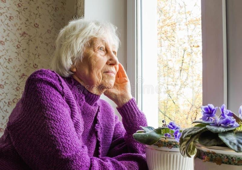 坐在窗口附近的老孤独的妇女在他的房子里 库存图片
