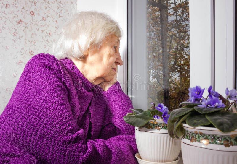 坐在窗口附近的老孤独的妇女在他的房子里 库存照片