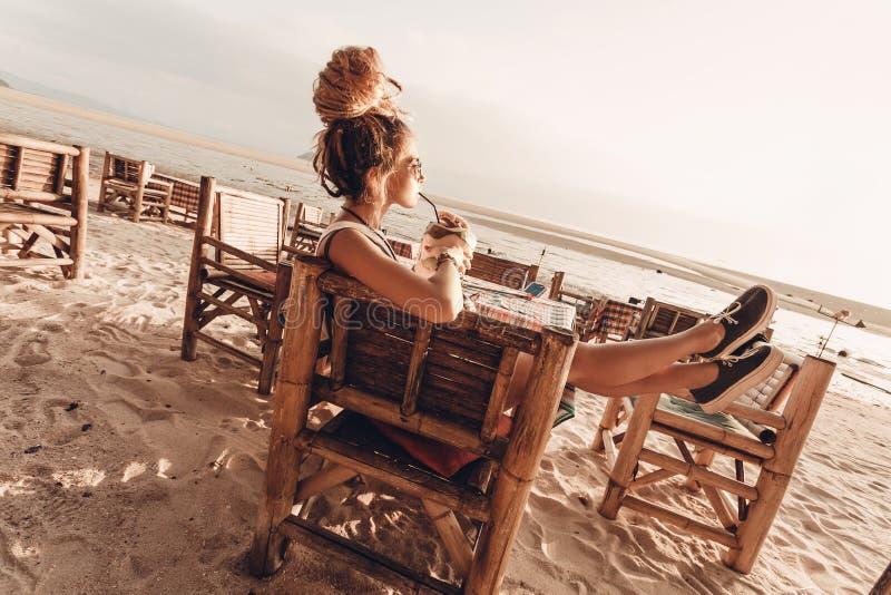 坐在竹椅子的年轻快乐的妇女在海滩在日落和饮用的椰子汁 免版税库存图片