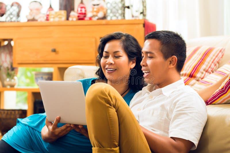 坐在笔记本笑前面的亚裔人民 免版税库存图片