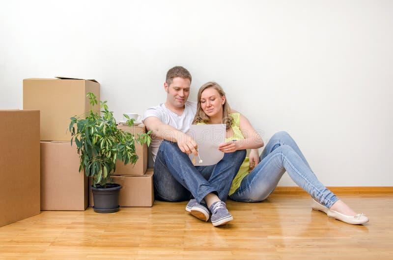 坐在箱子附近的愉快的家庭 免版税库存照片