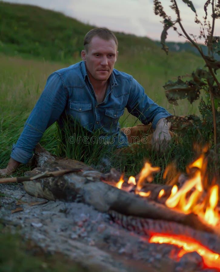 坐在篝火附近的人 免版税库存图片