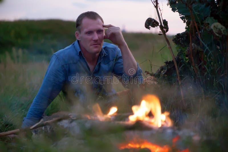 坐在篝火附近的人 免版税库存照片