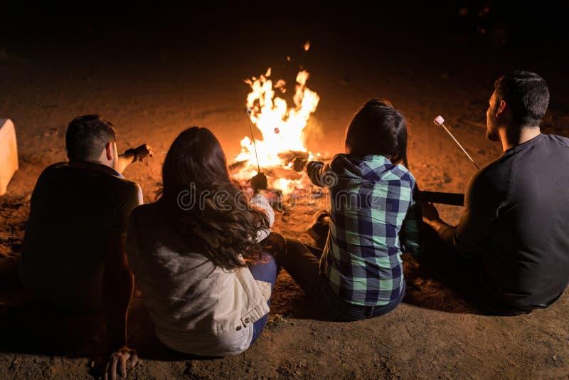 坐在篝火附近的小组朋友 免版税库存照片