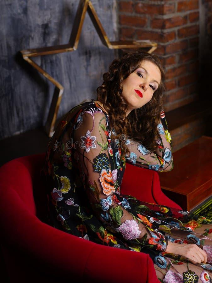 坐在红色扶手椅子的一个美丽的女孩的减速火箭的样式照片 库存图片