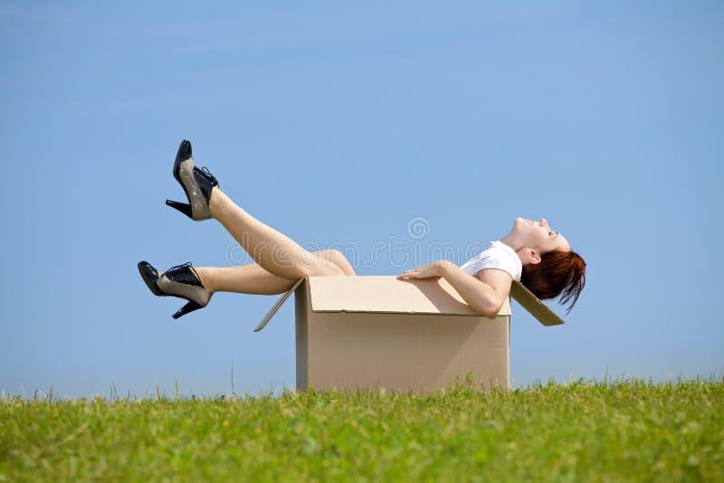 坐在纸板箱的少妇在公园 免版税库存图片