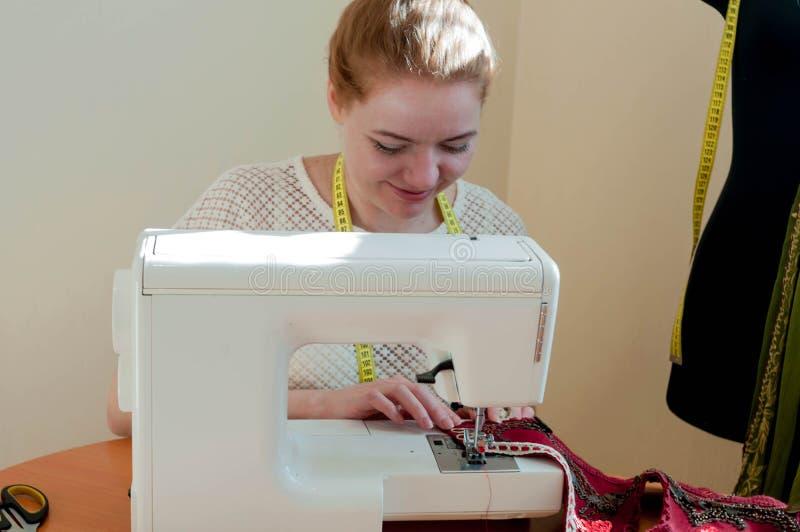 坐在缝纫机和工作在演播室的裁缝 免版税图库摄影