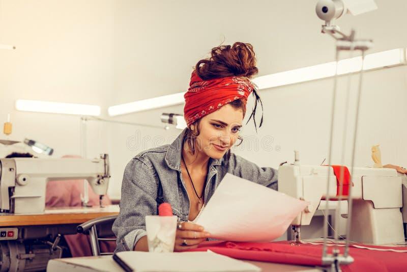 坐在缝纫机和微笑附近的Tailoress 免版税库存图片