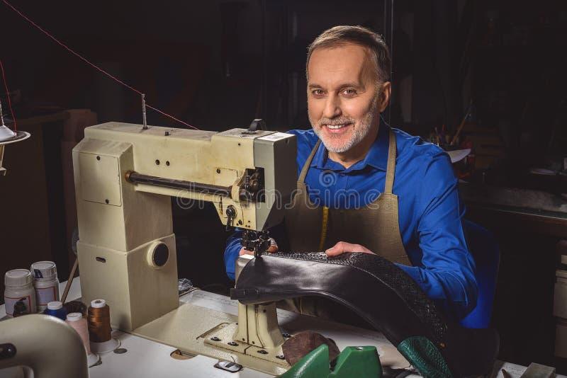 坐在缝纫机的愉快的鞋匠 免版税库存图片