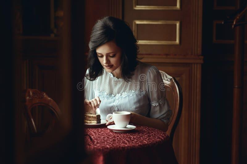 坐在美味的咖啡馆的桌上和切除可口巧克力蛋糕的片断年轻美女 免版税库存照片