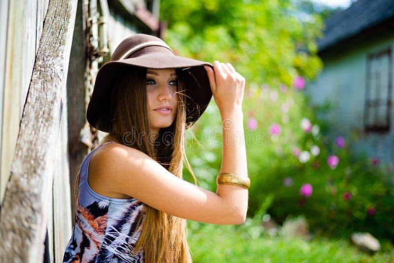 坐在老木旁边的棕色帽子的俏丽的女孩 库存照片