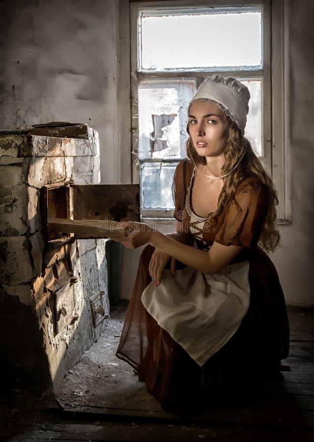 坐在老火炉旁边的一件土气礼服的妇女在一个被破坏的被放弃的房子里 免版税库存图片