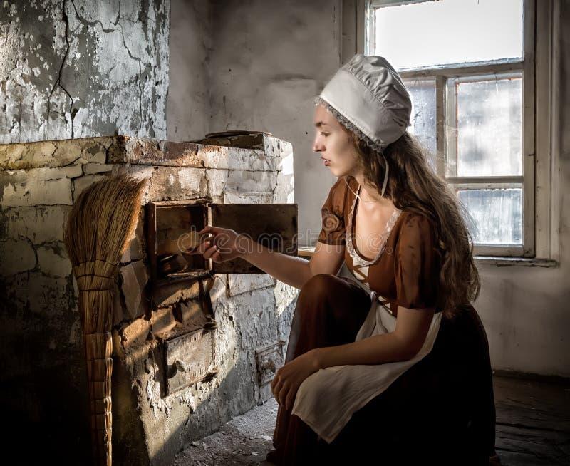 坐在老火炉旁边的一件土气礼服的妇女在一个被破坏的被放弃的房子里 库存图片