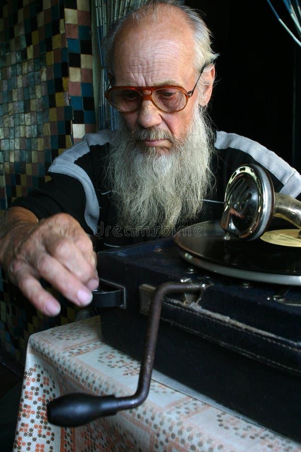 坐在老留声机旁边的年长人 库存照片