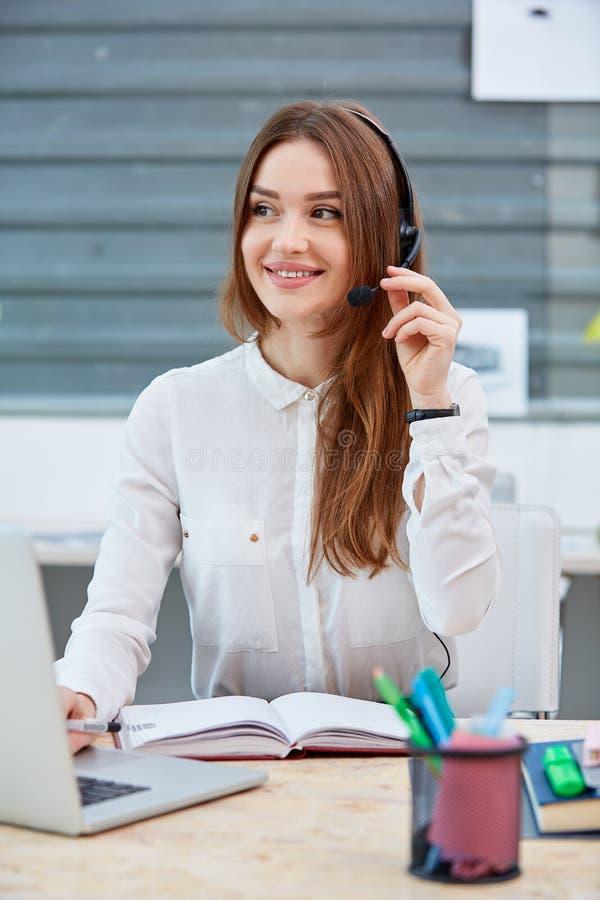 坐在耳机的书桌的女孩办公室工作者有膝上型计算机和微笑的 免版税库存图片