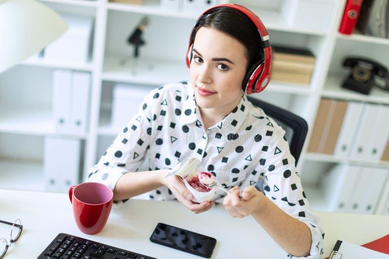 坐在耳机的美丽的女孩在书桌在吃与红色装填的办公室酸奶 图库摄影