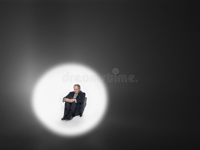 坐在聚光灯的商人 免版税库存照片
