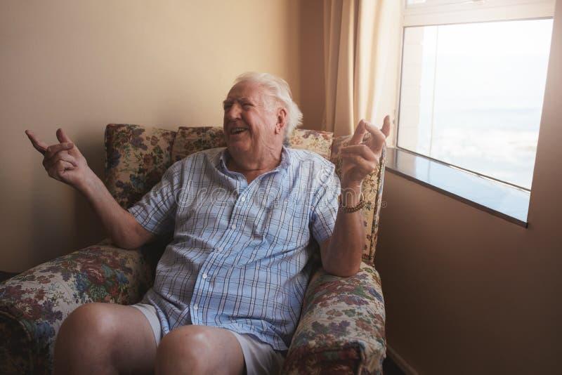 坐在胳膊椅子的老人 免版税库存照片