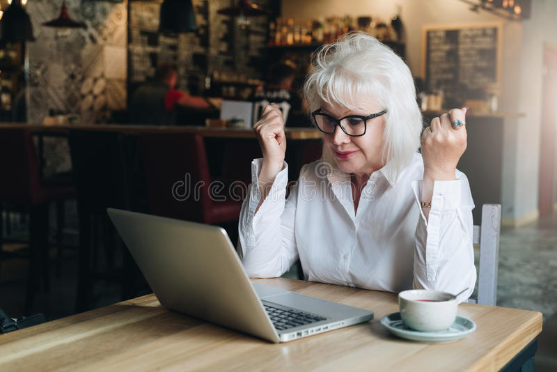 坐在膝上型计算机前面的桌上,握手和看显示器的愉快的女商人 好消息 免版税库存图片